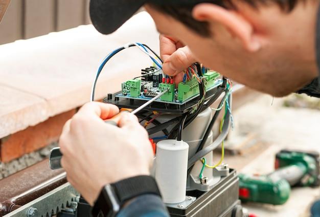 Homem técnico instalando e verificando o funcionamento do portão automático
