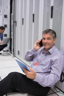 Homem telefonando enquanto faz a manutenção e segurando o tablet