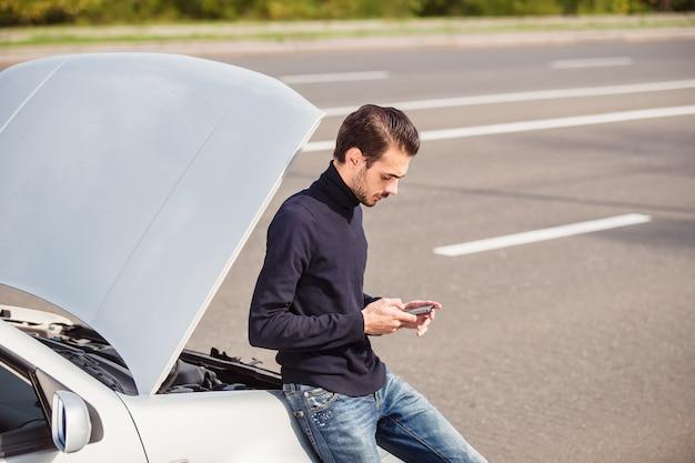 Homem telefonando para obter ajuda com o carro danificado
