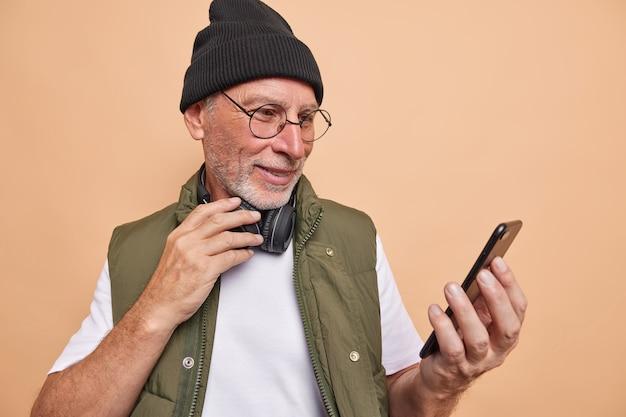 Homem telefone usuário navega internet faz videochamada usa fones de ouvido estéreo usa boné camiseta e colete óculos transparentes poses em marrom