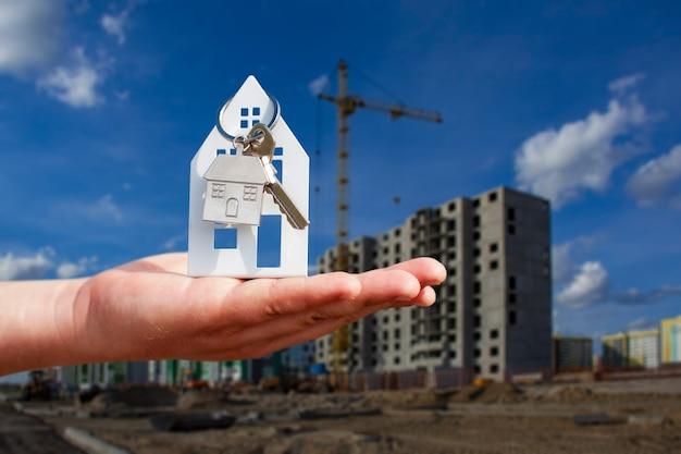 Homem tem as chaves da casa nas mãos no contexto de um edifício de vários andares. conceito de compra e aluguel de apartamentos.