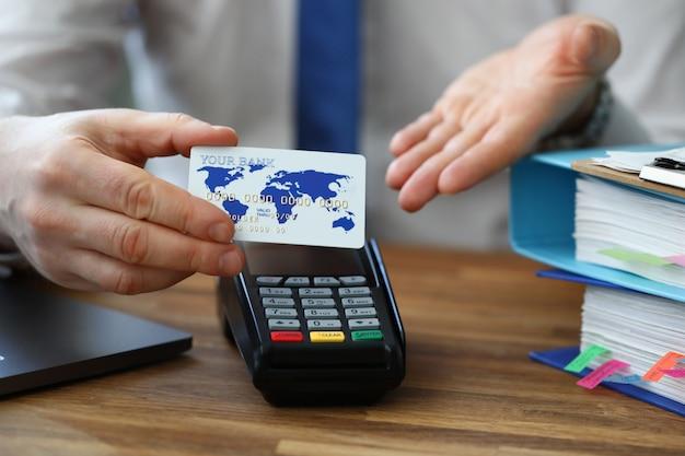 Homem tem cartão de crédito na mão, perto do terminal