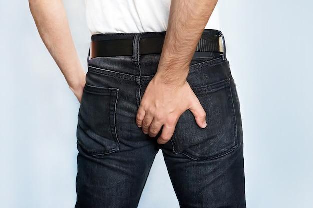 Homem tem diarreia segurando a bunda. cara para segurar com a mão uma bunda dolorida. a mão arranhando um lugar causal.
