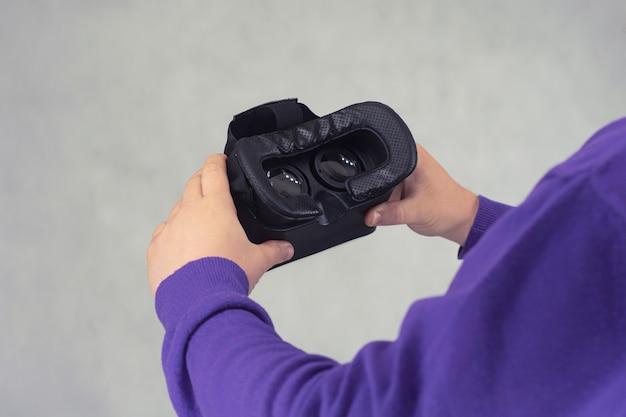 Homem tem em suas mãos óculos para realidade virtual e vídeo de 360 graus. capacete de vr para o smartphone em um fundo claro.