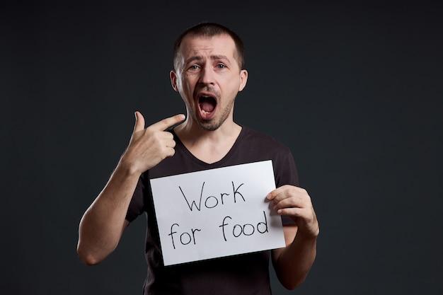 Homem tem nas mãos uma folha de papel de pôster com a inscrição eu trabalho por comida. sorriso e alegria, lugar para texto, espaço de cópia