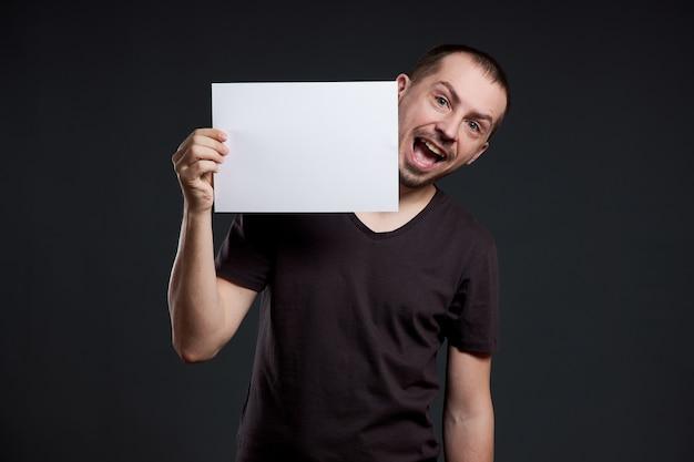 Homem tem nas mãos uma folha de papel de pôster vazia. sorriso e alegria, lugar para texto, espaço de cópia