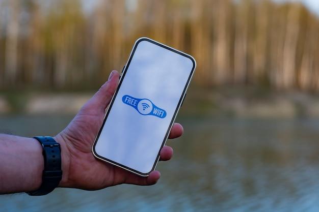 Homem tem um smartphone na mão com um ícone de wi-fi grátis no visor. telefone no fundo da floresta e do lago. acesso gratuito à internet na natureza.