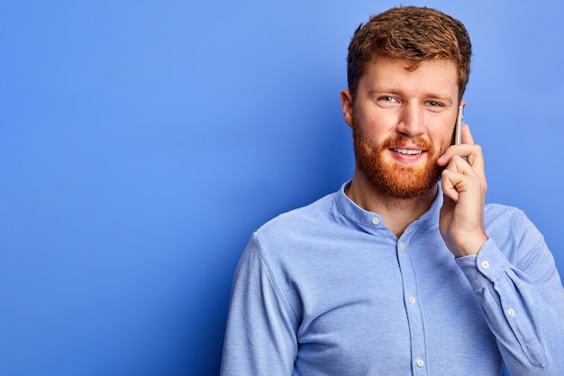 Homem tem uma boa conversa com alguém no telefone, vestindo camisa formal azul, tendo barba e cabelo ruivos, isolado sobre o espaço azul
