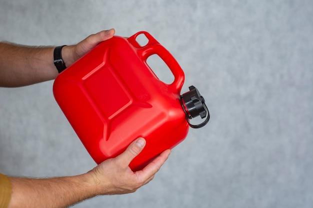 Homem tem uma botija de gás de plástico vermelho nas mãos.