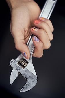 Homem tem uma chave inglesa na mão, manicure com um padrão nos dedos de um homem. cuidados com as unhas das mãos