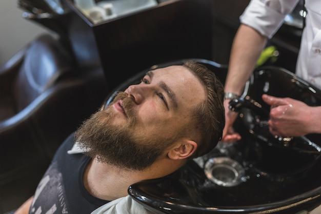 Homem, tendo, cabelo, lavado, barbeiro
