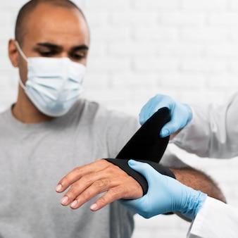Homem tendo o pulso enfaixado por fisioterapeuta