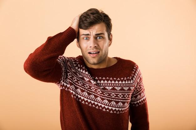 Homem tenso com a barba por fazer, vestindo um suéter de tricô agarrando a cabeça, isolado sobre uma parede bege
