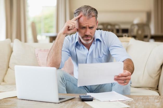 Homem tenso olhando as contas na sala de estar
