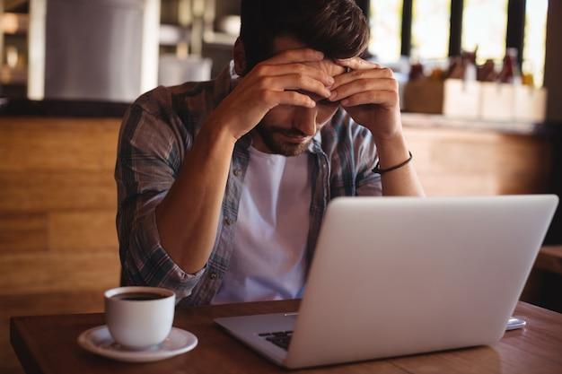 Homem tenso sentado com laptop