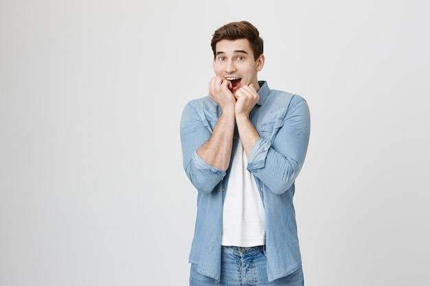 Homem tentador e animado roendo unhas e olhando com desejo