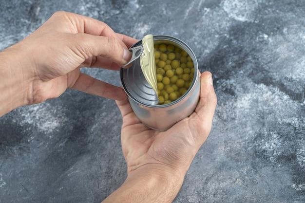 Homem tentando abrir a lata. ervilhas verdes.