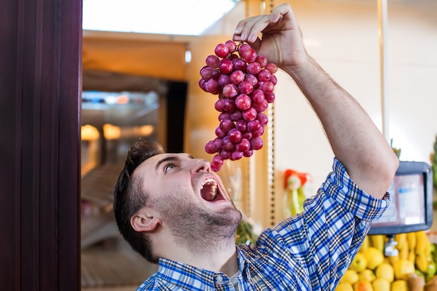Homem tentando comer um cacho de uvas.