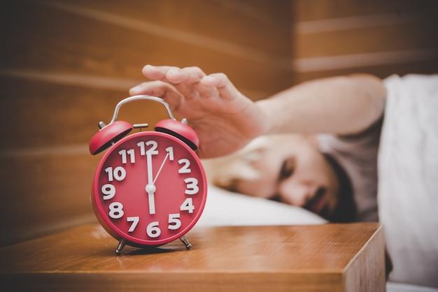 Homem tentando desligar o despertador acordando de manhã.