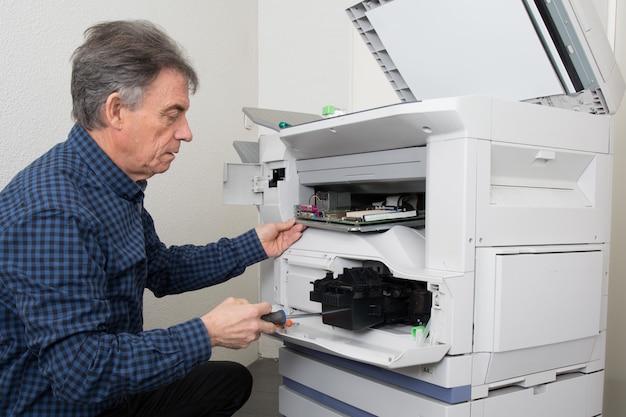 Homem tentando reparar a impressora de escritório no trabalho