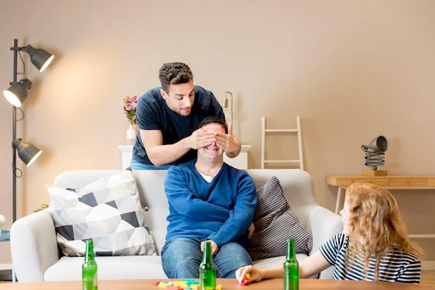 Homem tentando surpreender amigos em casa