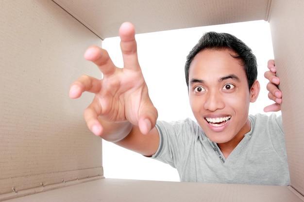Homem tentando tirar algo dentro da caixa