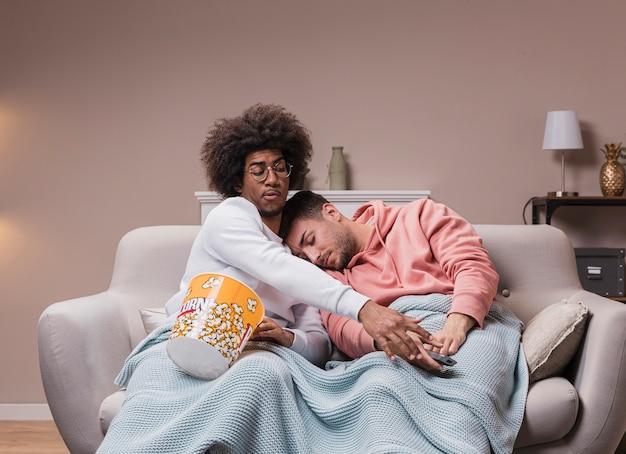 Homem tentando tirar o controle remoto enquanto amigo dormindo
