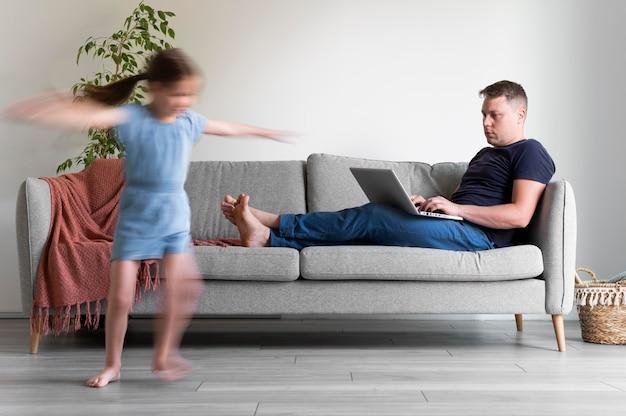 Homem tentando trabalhar em um laptop de casa enquanto os filhos dela estão correndo