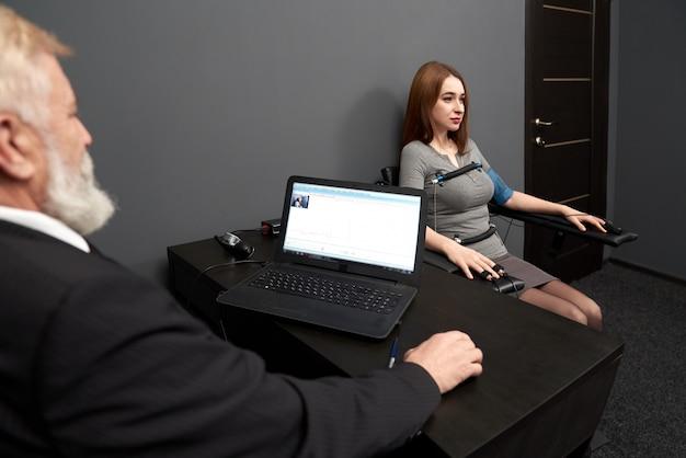 Homem testando amplitude, pulso de mulher com polígrafo.