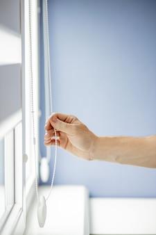 Homem testando persianas de rolo em janelas
