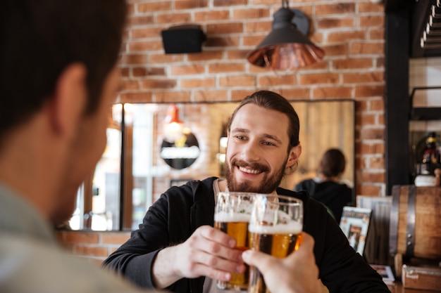 Homem tilintar de copos com amigo no bar