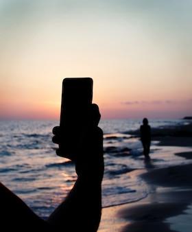 Homem tira foto de namorada ao pôr do sol no celular