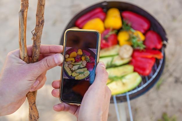 Homem tira fotos no telefone de vegetais grelhados. vegetais, pimentão vermelho e amarelo, cogumelos e abobrinha assados em uma churrasqueira redonda