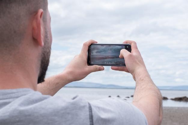 Homem tirando foto com o celular na praia. vista das montanhas ao longe