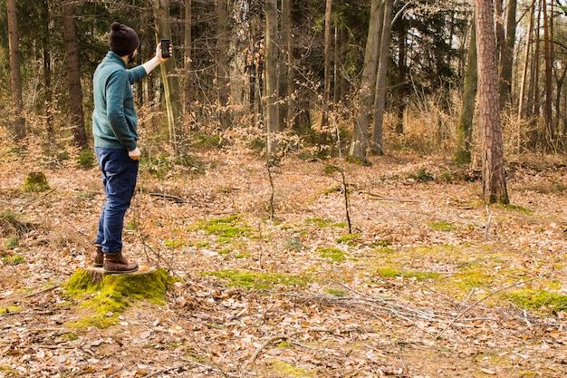 Homem tirando foto com smartphone na floresta