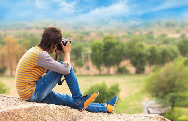 Homem tirando foto da câmera em paisagem em um dia ensolarado