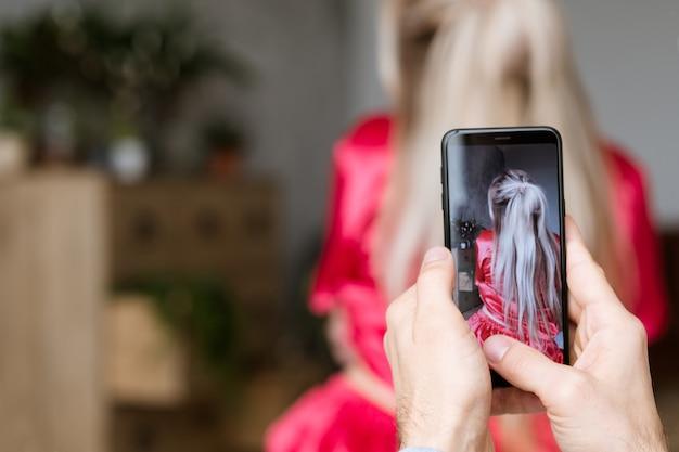 Homem tirando foto da namorada com smartphone, vista traseira