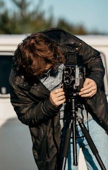 Homem tirando foto da namorada com uma câmera retro