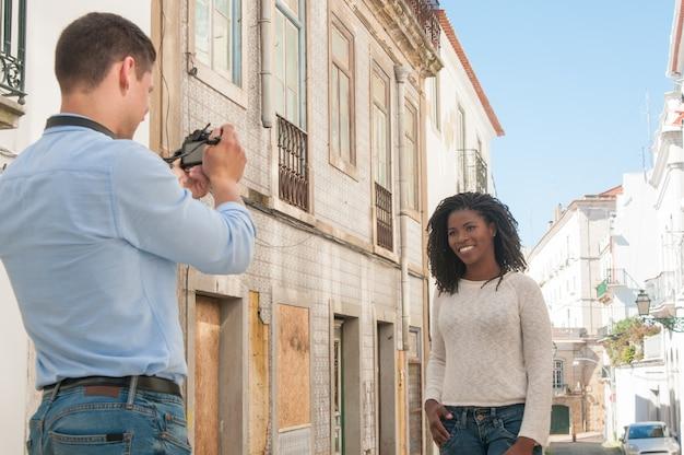 Homem tirando foto de mulher negra feliz ao ar livre