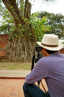 Homem tirando fotos da cabeça da estátua de buda presa nas raízes das árvores bodhi, tailândia