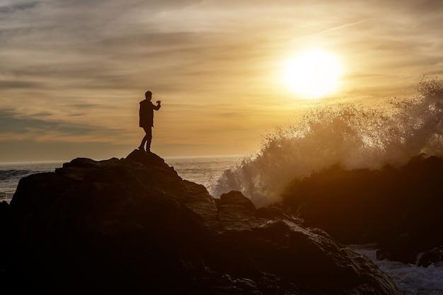 Homem tirando fotos de ondas em um penhasco com o smartphone
