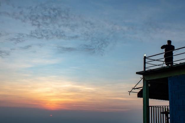 Homem tirando fotos de um belo nascer do sol da manhã.