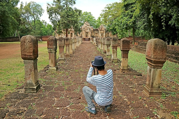 Homem tirando fotos do templo prasat sdok kok thom khmer, província de sa kaeo, tailândia