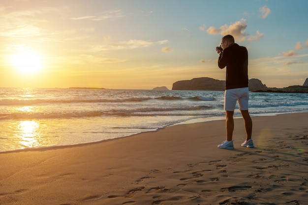 Homem tirando fotos em uma praia tropical durante o pôr do sol