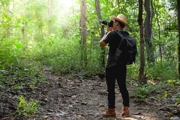Homem tirando fotos na floresta