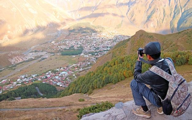 Homem tirando fotos vistas aéreas da cidade de kazbegi a partir da igreja da trindade de gergeti, geórgia
