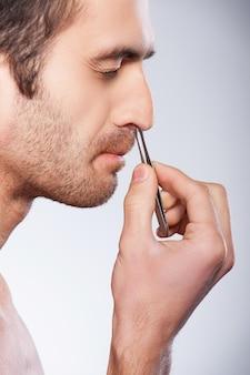 Homem tirando o cabelo do nariz. vista lateral de um jovem afastando o cabelo do nariz e mantendo os olhos fechados em pé contra um fundo cinza