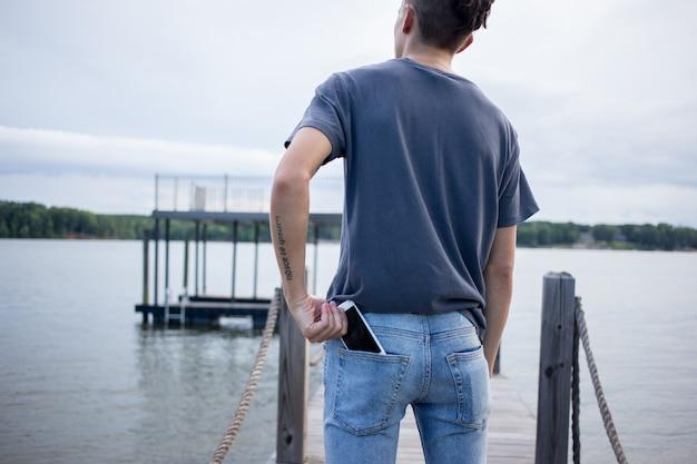 Homem tirando o smartphone do bolso de trás.