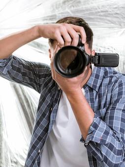 Homem tirando uma foto com uma câmera profissional
