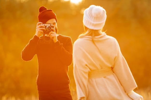 Homem tirando uma foto de seu amigo ao ar livre
